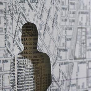 Identidades Veladas, 2019   Collage de siluetas caladas sobre guías telefónicas y planos de ciudad   180 x 250 cm.