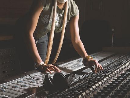 Mujer que trabaja en la consola de mezcl