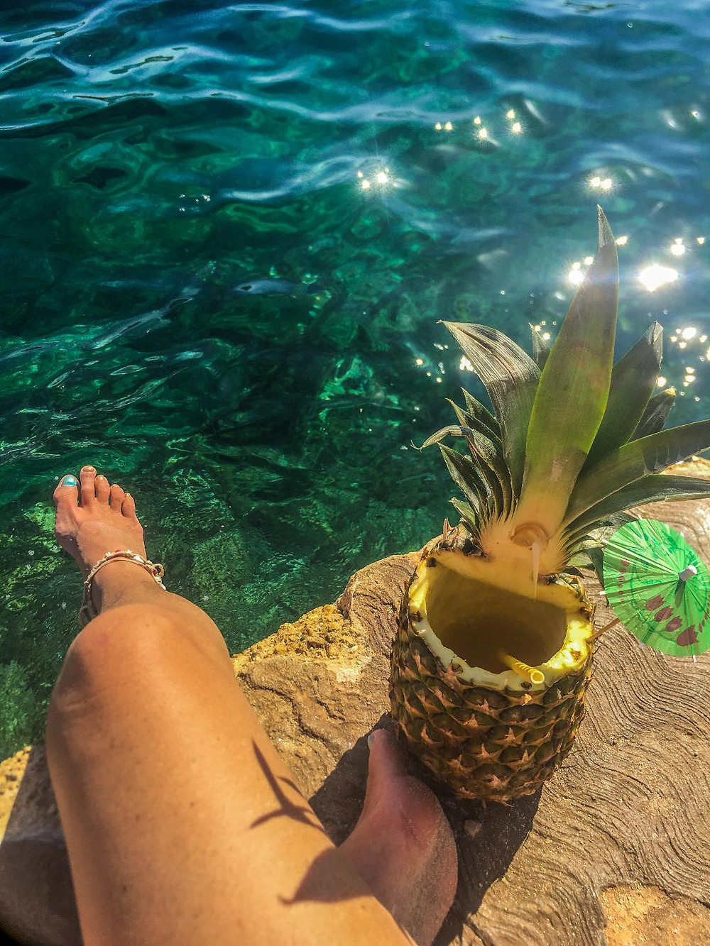 Cocktail within a pineapple with umbrella