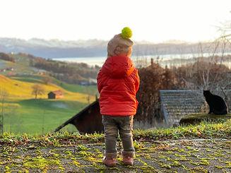 Kleines Mädchen mit Mütze blickt in Hügellandschaft