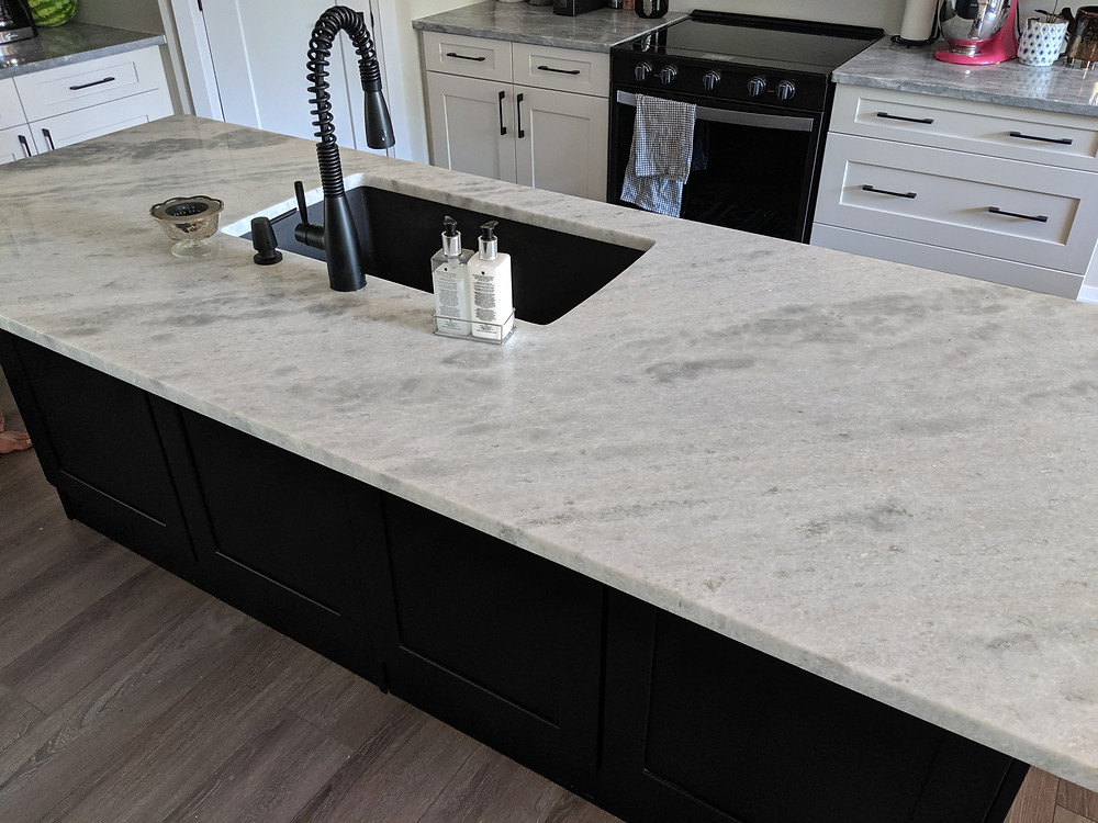 White stone counter top and new appliances in kitchen renovation