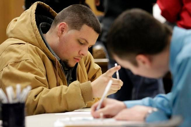 Tyler Kelly, 19, left, fills out applications for parking enforcement and environmental compliance jobs during a public safety job fair at City Hall in Saginaw, Mich. (AP file)