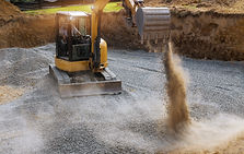Excavator bucket moving gravel stones fo
