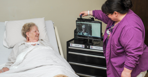 Nurse Practitioner visits with patient and nurse's aide