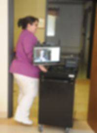 Nurse wheels telemedicine cart to another room