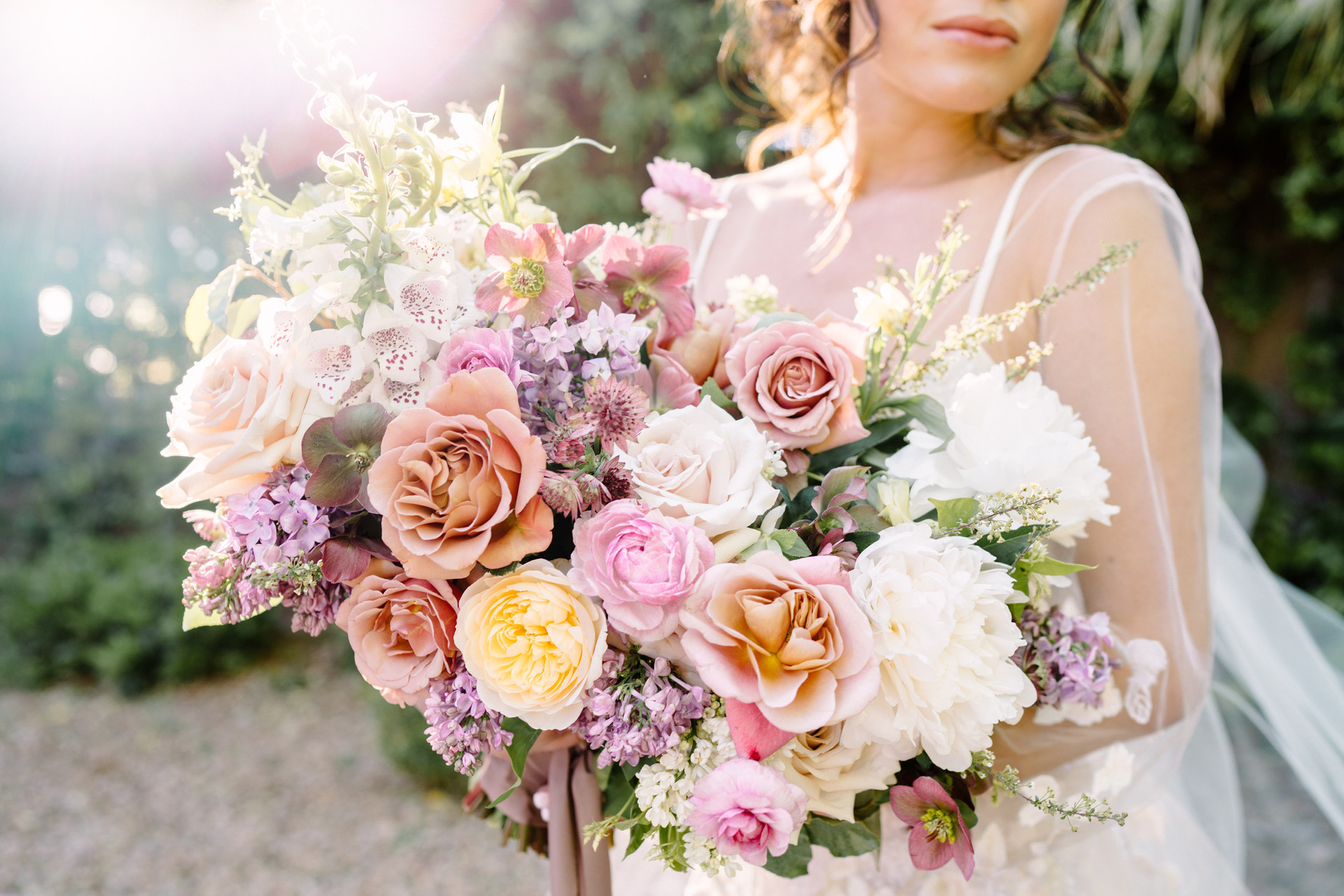 Colorful garden-style bouquet with foxglove, roses, peonies, lilac, hellebores, and ranunculus. Photo: Gaby Jeter