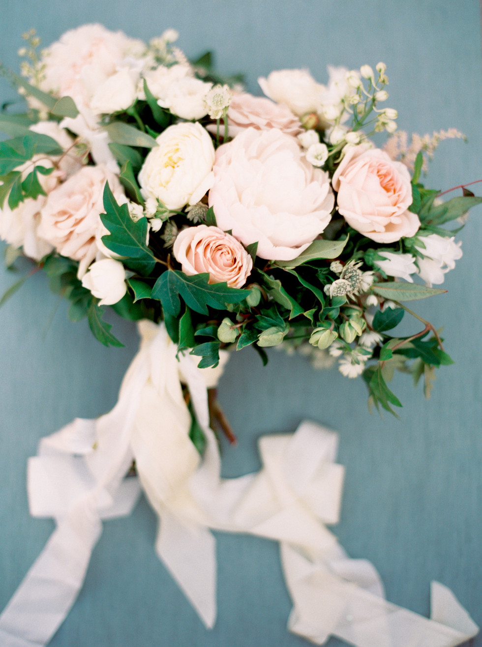 Blush and white garden-style bridal bouquet with silk ribbons. Photo: Mary Claire