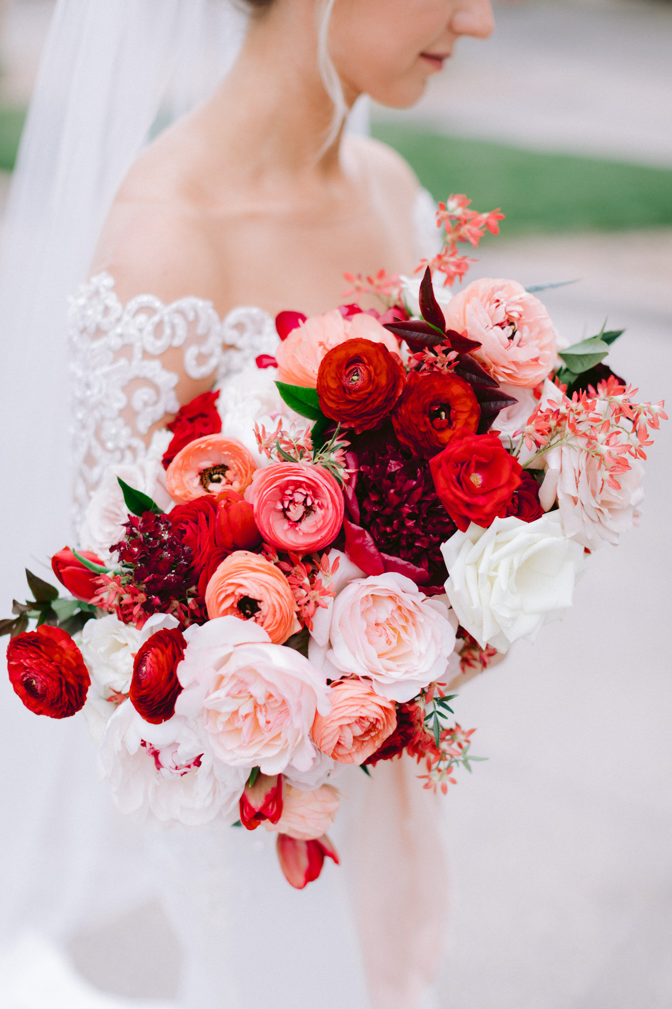 Blush and red bridal bouquet with peonies, garden roses, ranunculus, and tulips. Photo: Susie and Will