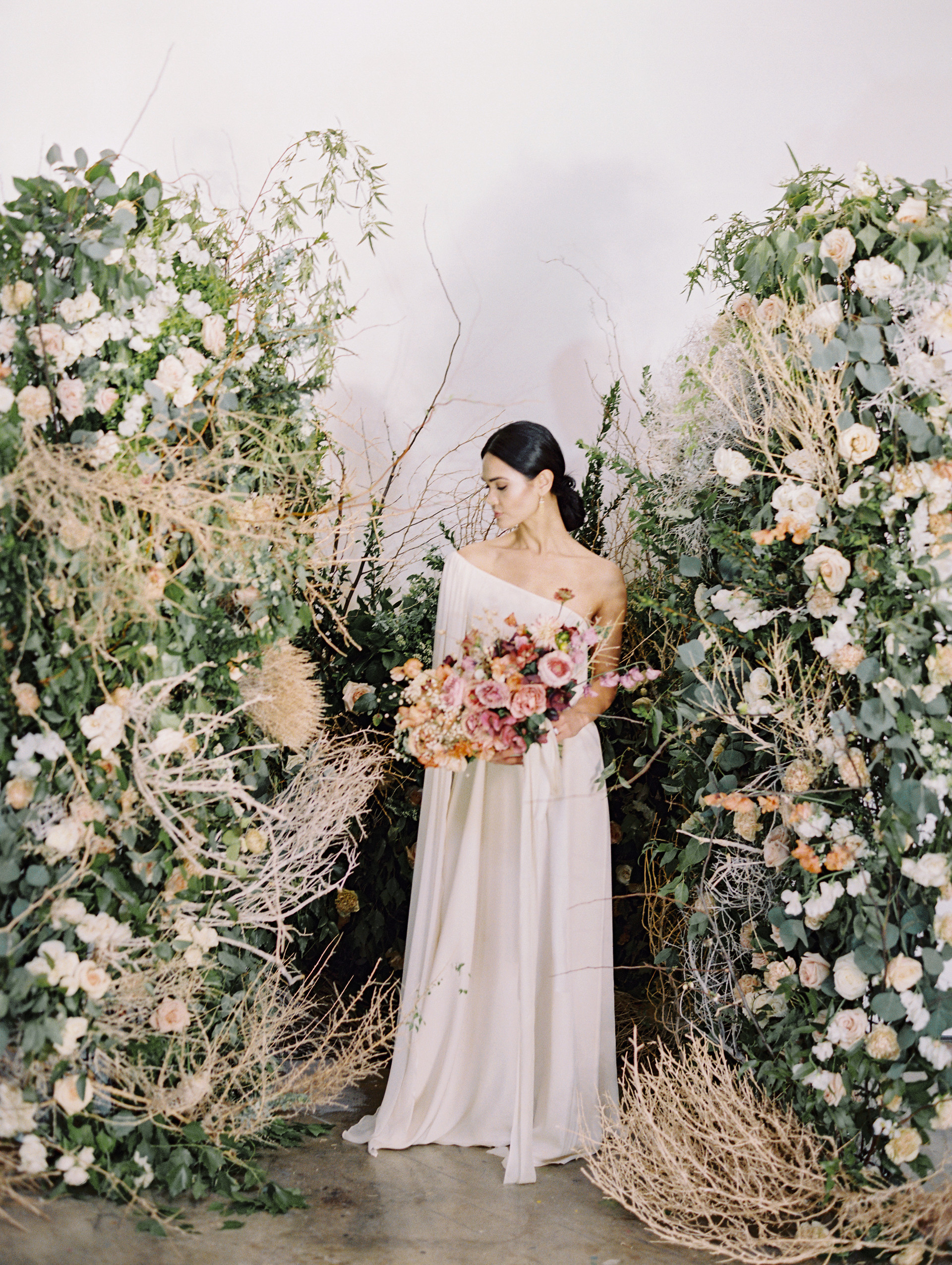 Rustic ceremony backdrop with tumbleweeds, fresh and dried floral. Photo: Gaby Jeter