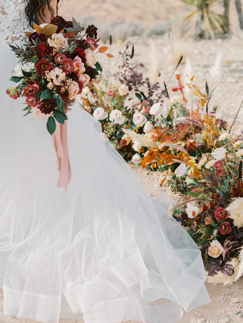 Ceremony florals with pampas grass, cat tails, dahlias, and fall leaves, in shades of burnt orange, burgundy, and ivory. Photo: Gaby Jeter