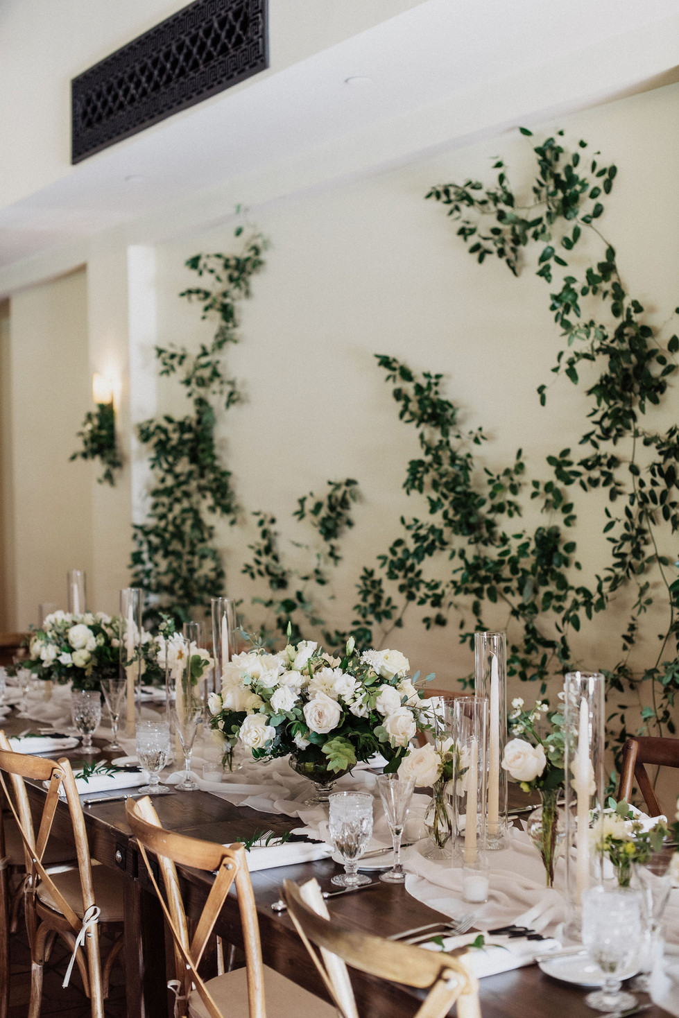 White and ivory centerpieces with greenery vines crawling up the walls. Photo: Eden Strider