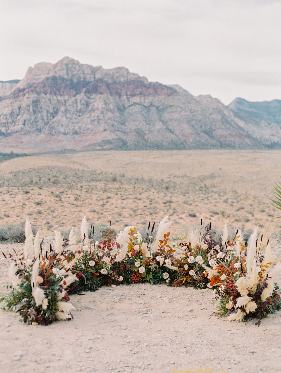 Half circle ceremony florals in Red Rock Canyon. Photo: Gaby Jeter