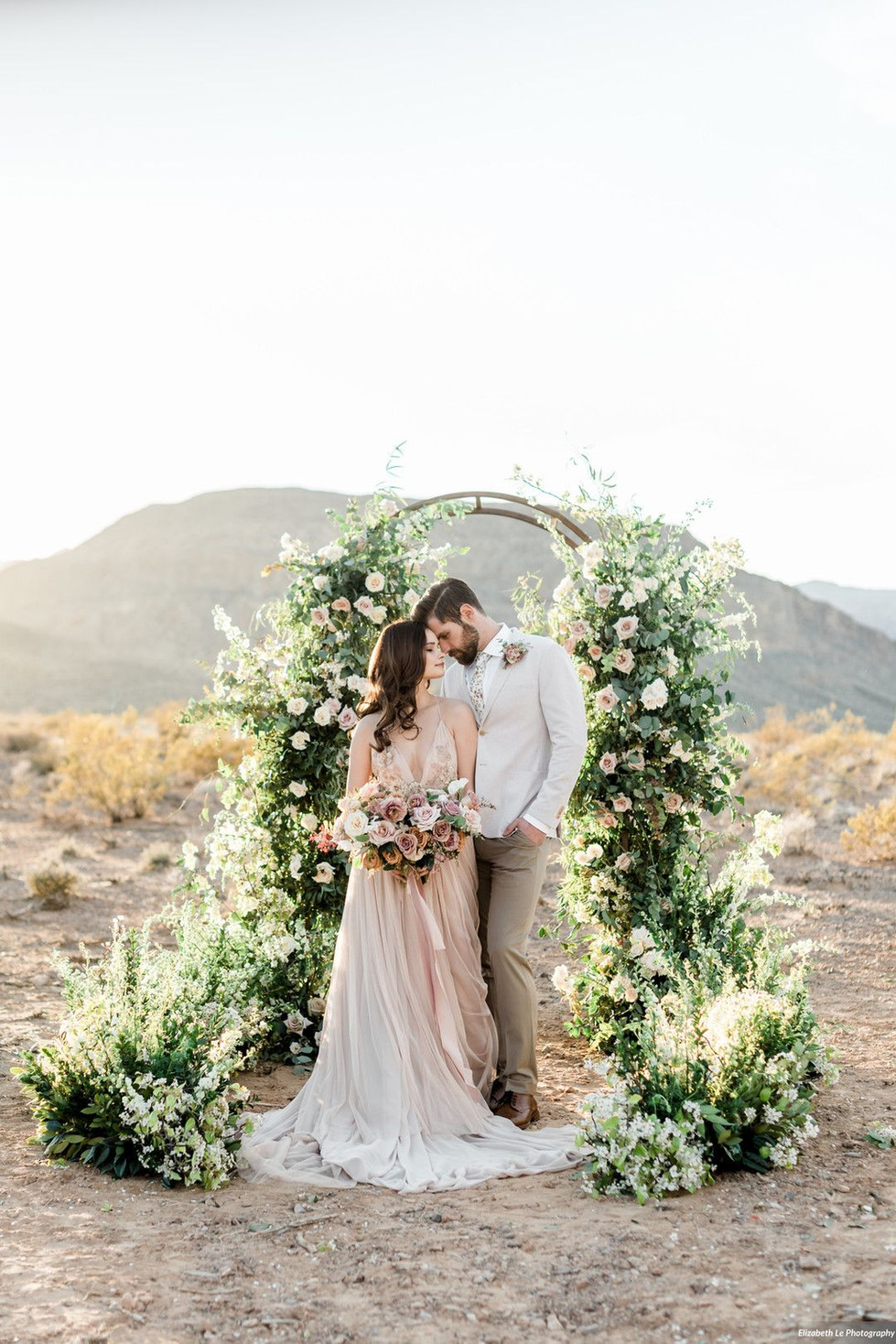 Lush ceremony arch in shades of dusy blush and mauve. Photo: Elizabeth Le