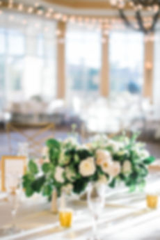 Low Wedding Centerpieces with White Flowes Designed in Gold Compote Vase