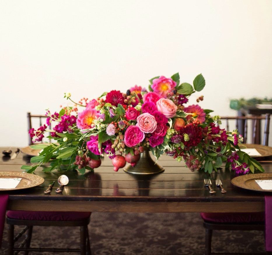 Berry-hued fall centerpiece with roses, dahlias, berries and pomegrantes. Photo: Rapp Photography