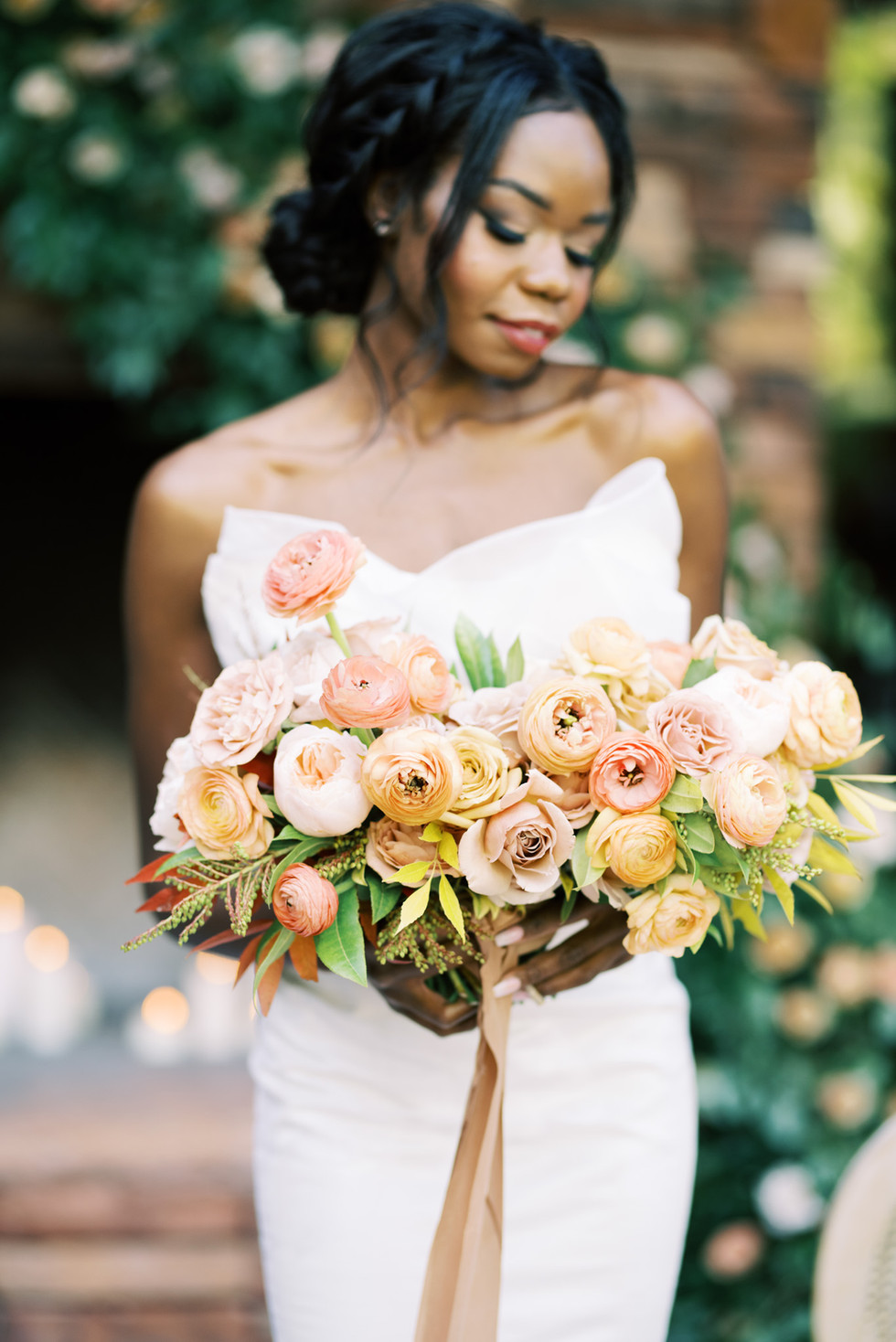 Bridal bouquet with roses and ranunculus in shades of coral, peach, taupe, and mustard. Photo: Kristen Kay