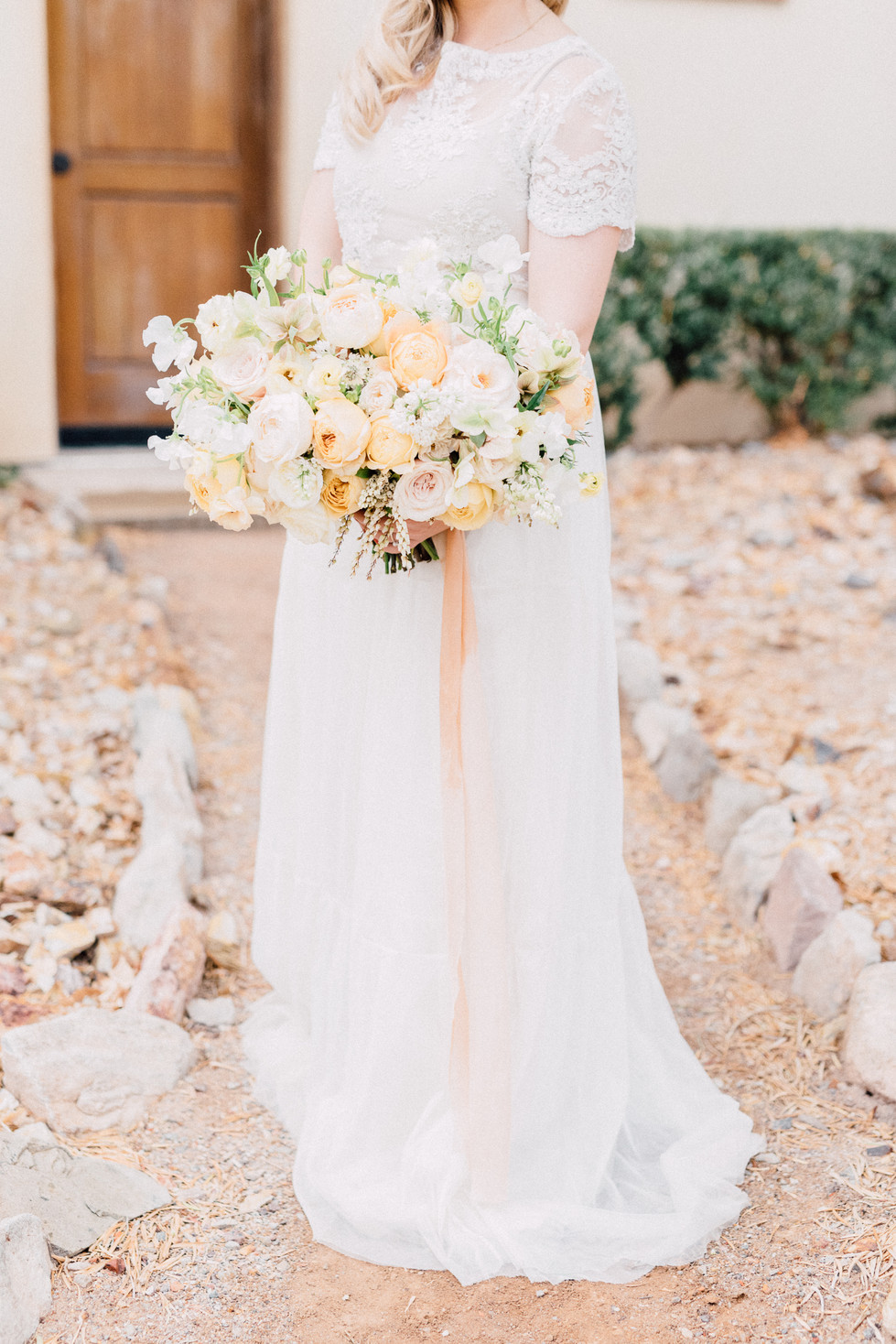 Soft yellow, blush and white bouquet, tied with silk ribbons. Photo: Kristen Joy