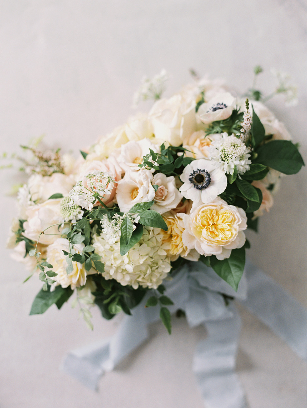 Garden-style bridal bouquet with roses, anemones, hydrangea, and lace flower. Photo: Gaby Jeter