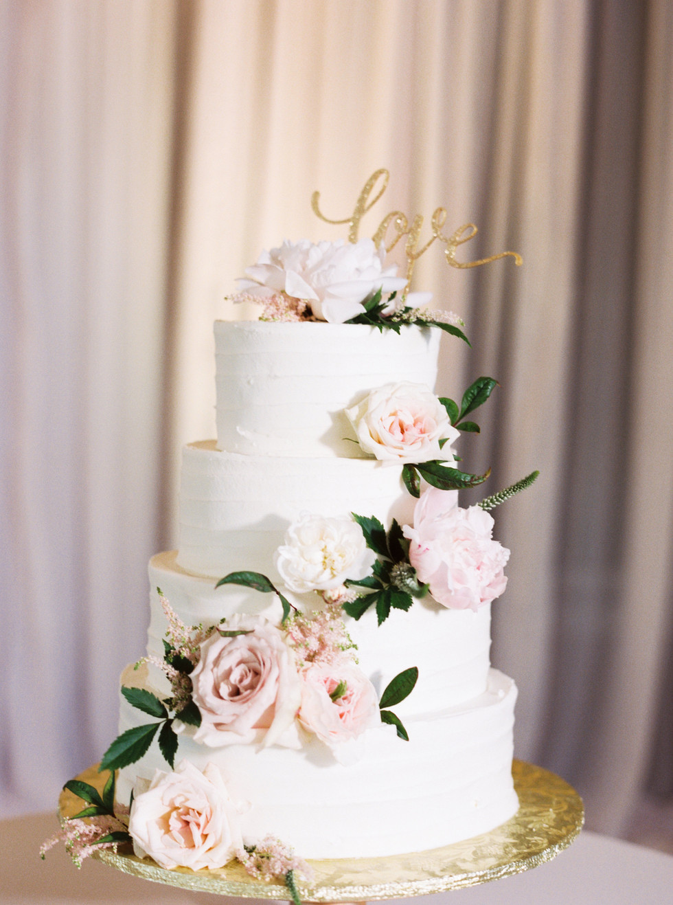 Cascading dusty blush roses and peonies on wedding cake. Photo: Mary Claire