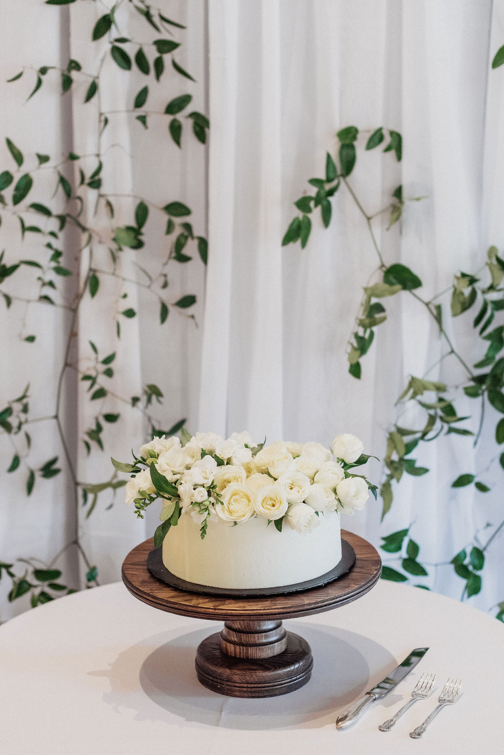 Trailing vines with miniature garden roses and fragrant freesia on wedding cake. Photo: Eden Strader