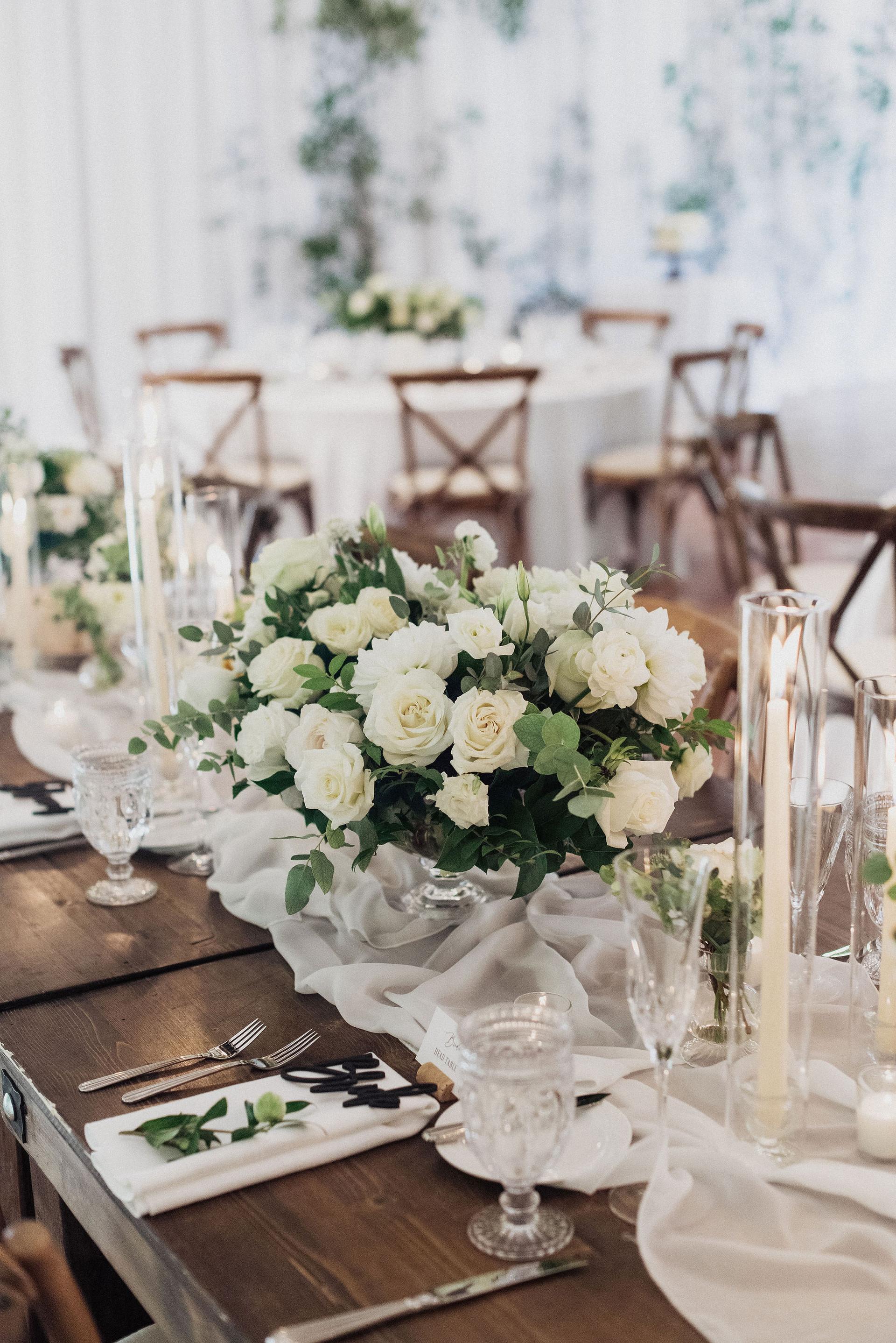 White and cream centerpieces with roses, dahlias, ranunculus, eucalyptus and vines. Photo: Eden Strader