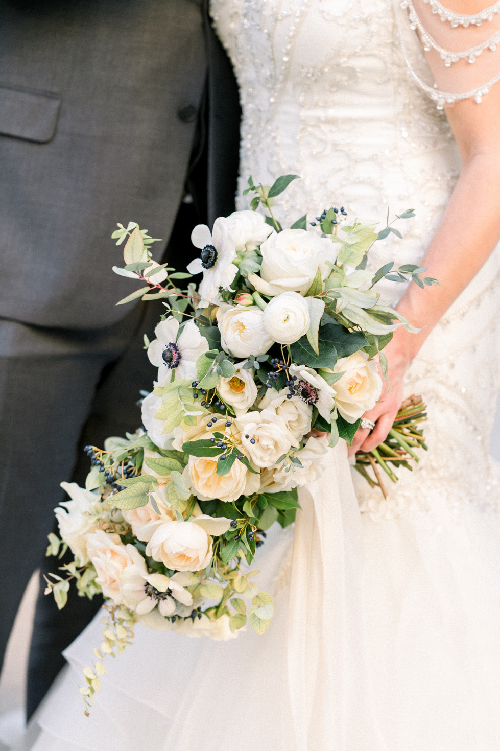WHITE AND CREAM BRIDAL BOUQUET WITH ROSES, RANUNCULUS, ANEMONES, AND BERRIES, TIED WITH ANTIQUE WHITE SILK RIBBONS. PHOTO: LIANNA MARIE