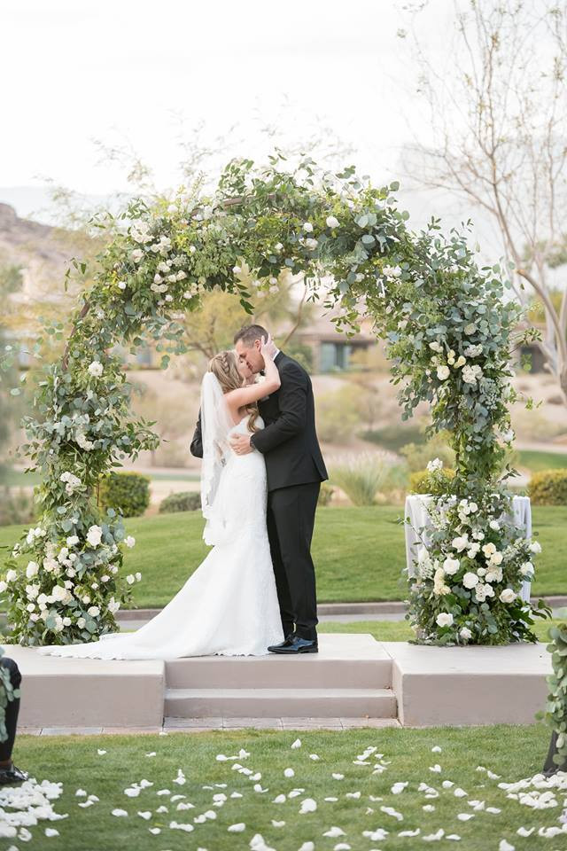 White and green ceremony arch, Red Rock Country Club. Photo: KMH Photography