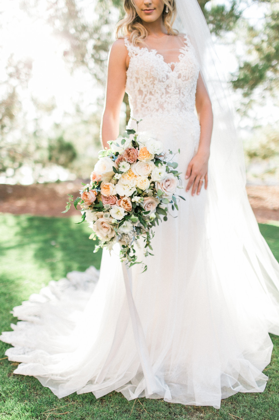 Bridal bouquet with garden roses, hellebores, ranunculus and dahlias in shades of ivory and blush. Photo: Lianna Marie