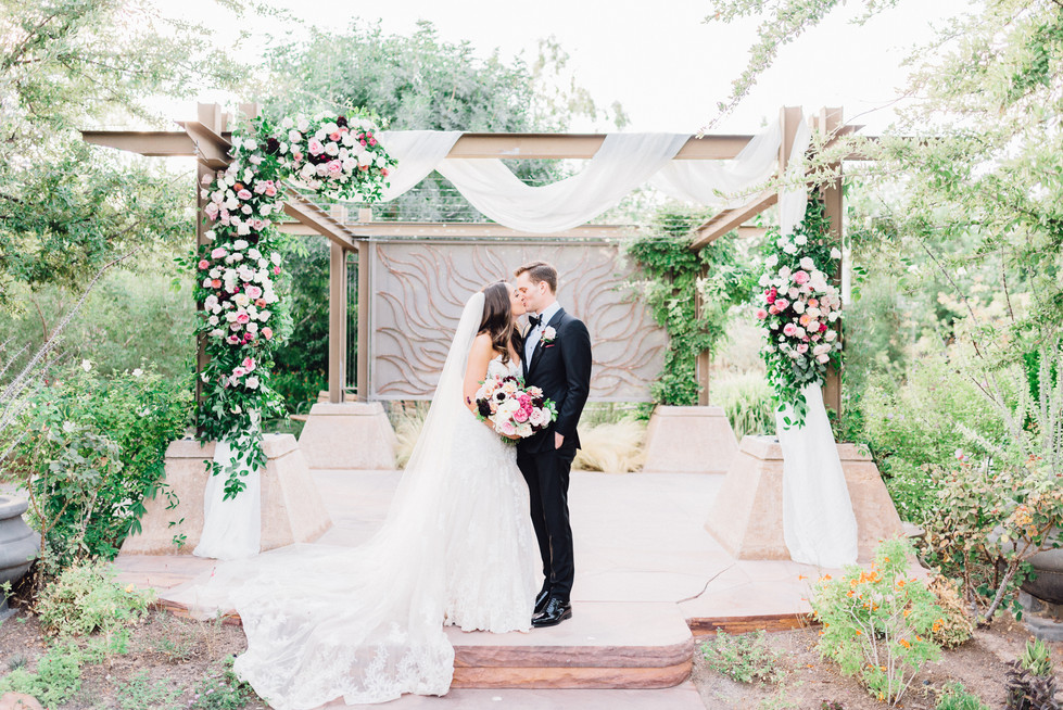 White chiffon fabric draped over arbor with clusters of roses in shades of pink. Photo: Kristen Joy