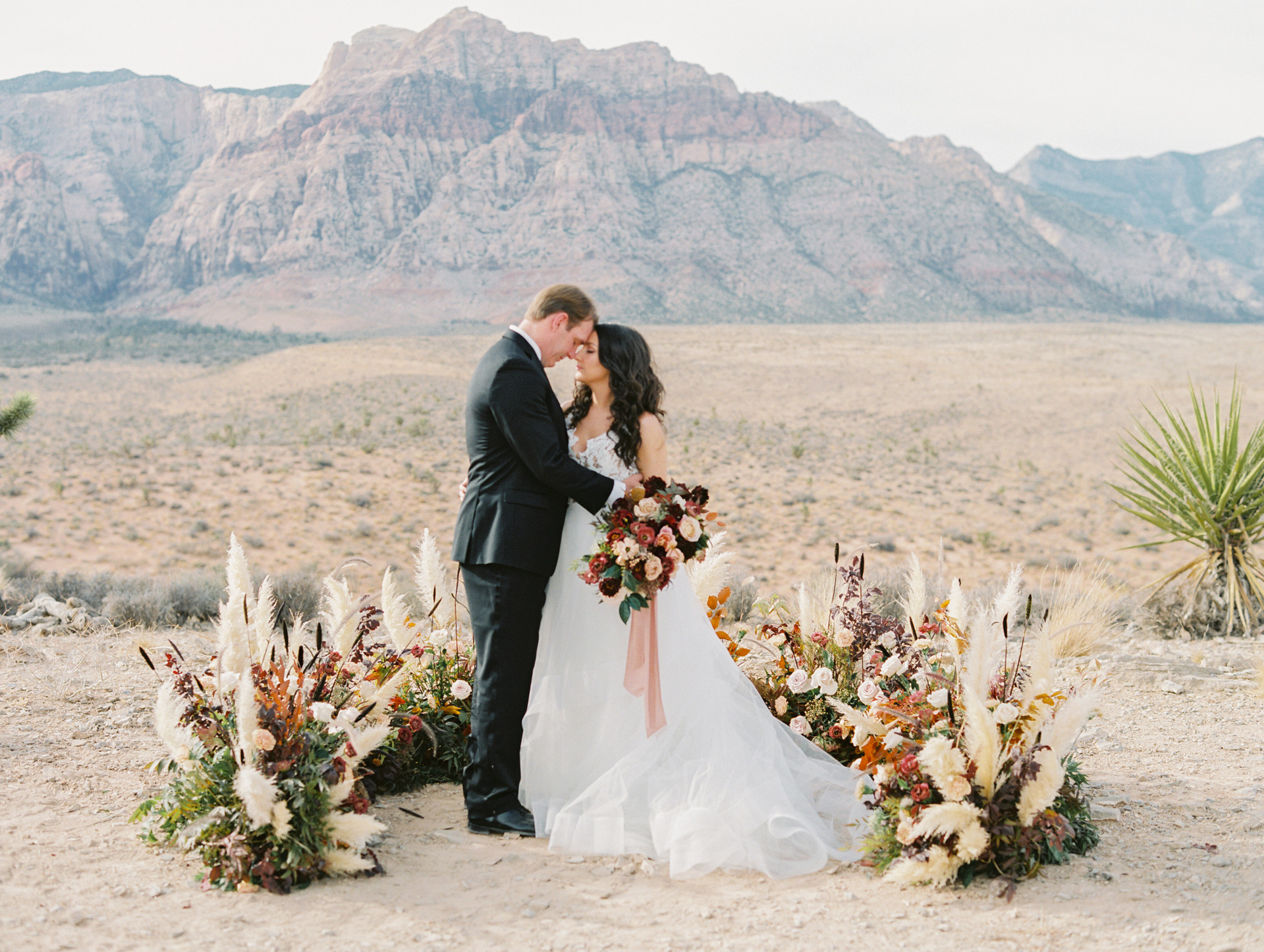 Half moon ceremony florals with pampas grass, florals, and fall foliage. Photo: Gaby Jeter