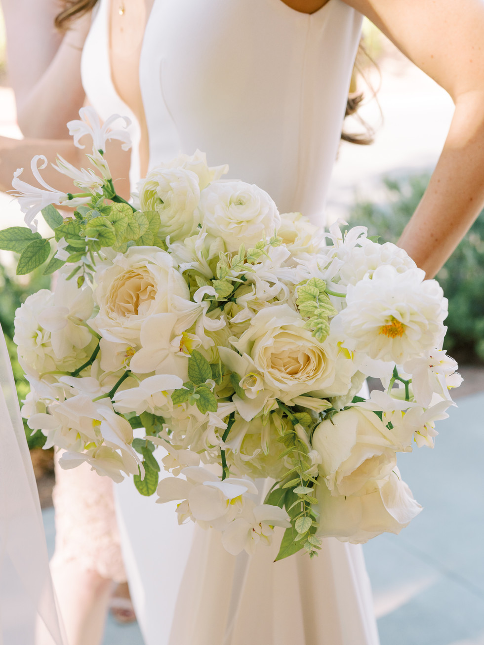 White bridal bouquet with garden roses, orchids, dahlias, and ranunculus. Photo: Gaby Jeter