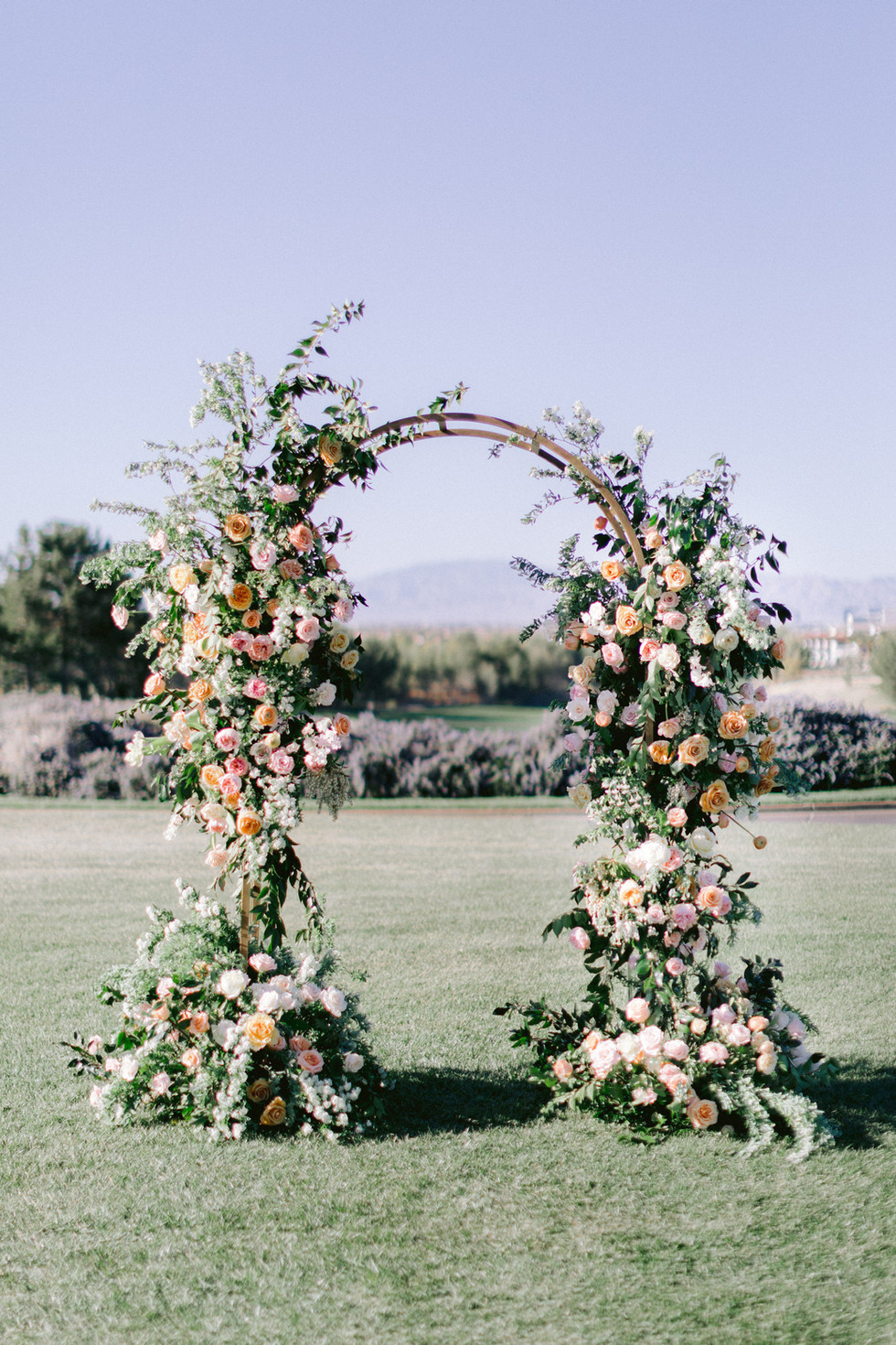 Peach, blush, and gold wedding arch. Photo: Susie and Will