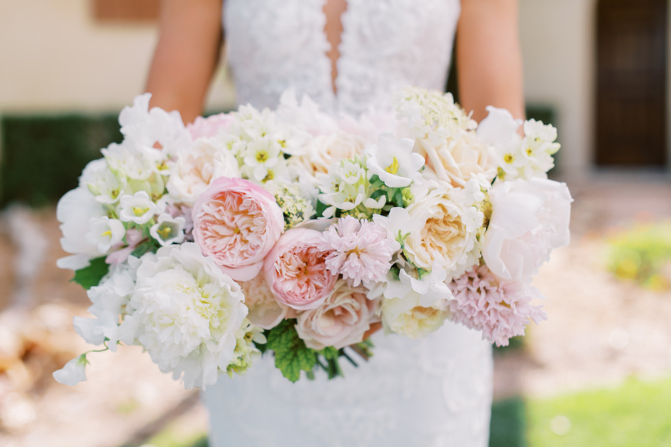 Blush and ivory bridal bouquet with garden roses, peonies, butterfly ranunculus, and hyacinth. Photo: Gaby Jeter