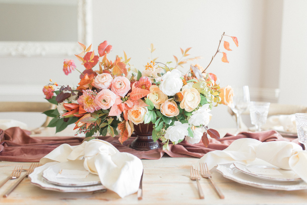 Fall centerpiece with garden roses, ranunculus, poinsettia and fall foliage. Photo: Elyse Alexandria