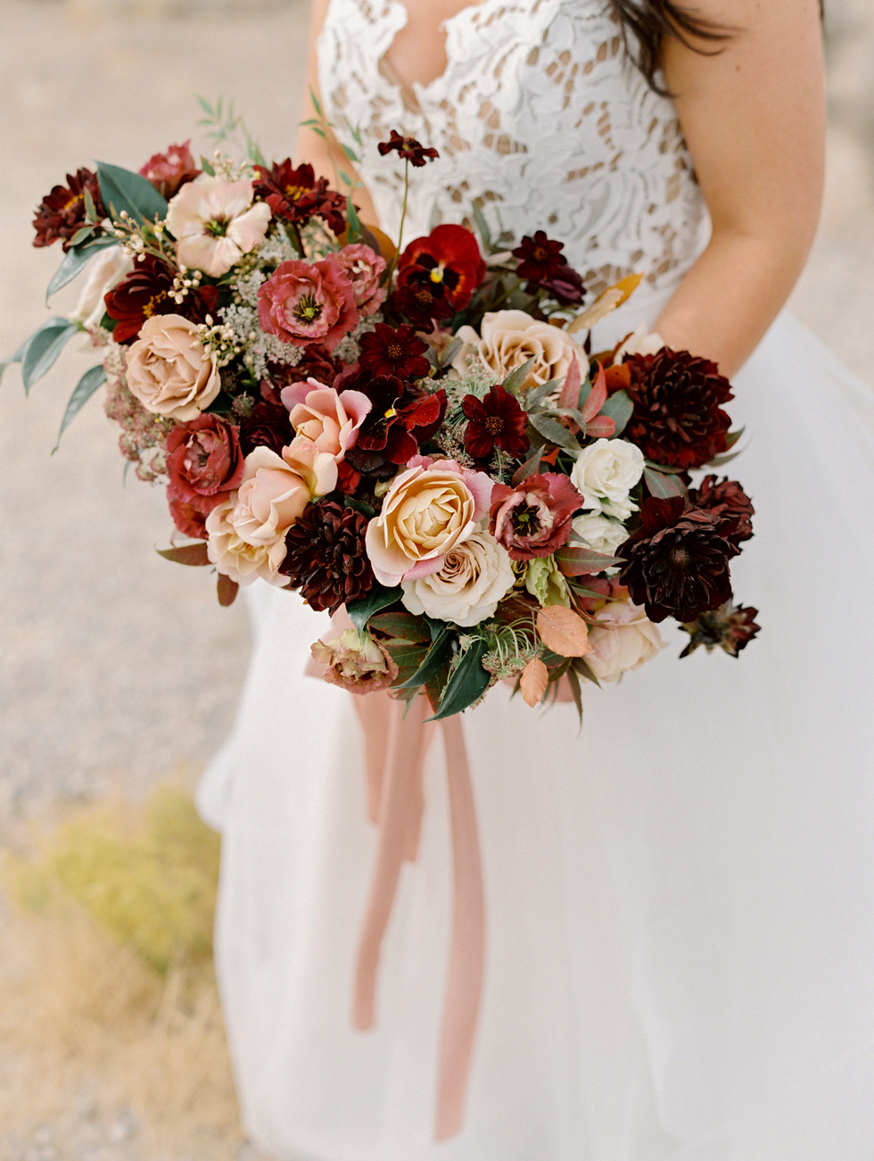 Burgundy, mauve and nude bridal bouquet with roses, dahlias, lisianthus, pansies, and chocolate cosmos. Photo: Gaby Jeter