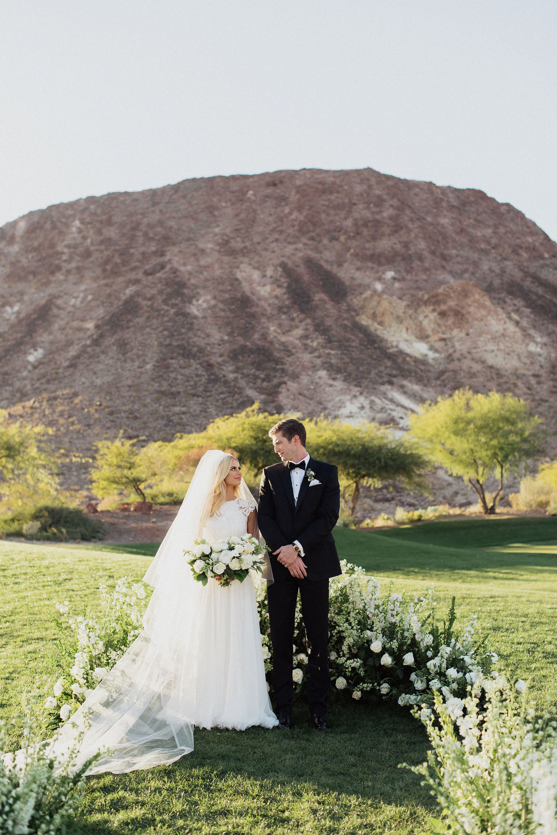 White and ivory semi circle ceremony floral. Photo: Eden Strider