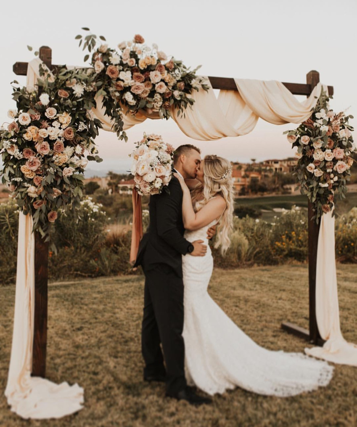 Wedding arch in shades of blush, mauve and taupe. Photo: Sunny Heers