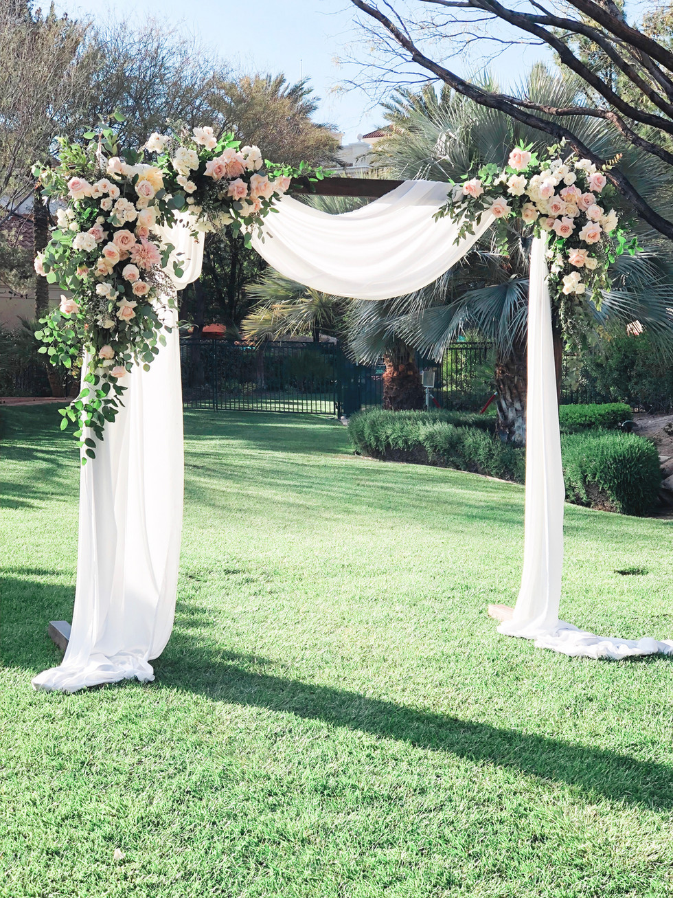 Wedding arch with blush and white flowers and loosley draped fabric.