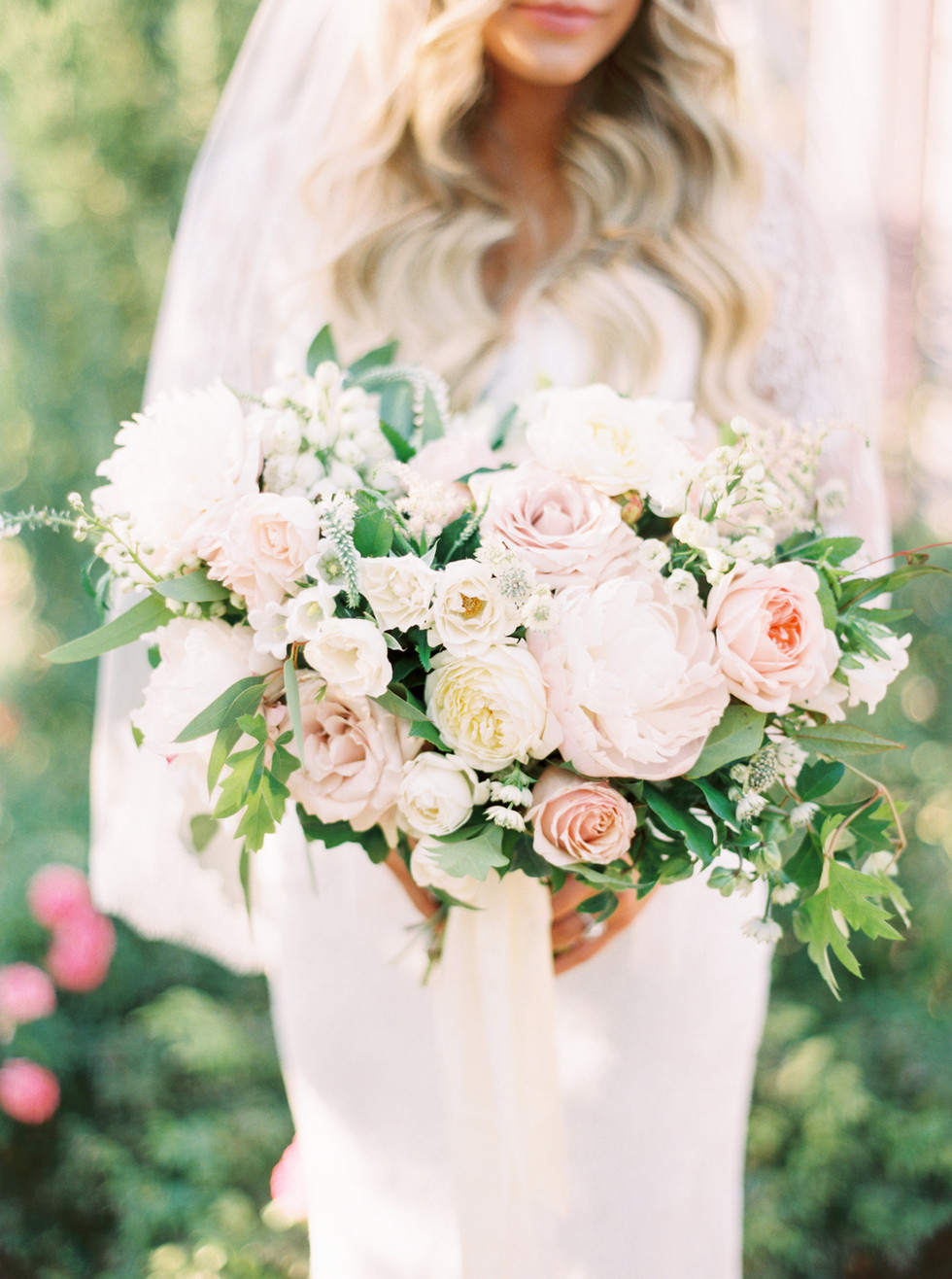 Blush and ivory bridal bouquet with peonies, roses and garden greenery, tied with silk ribbons. Photo: Mary Claire