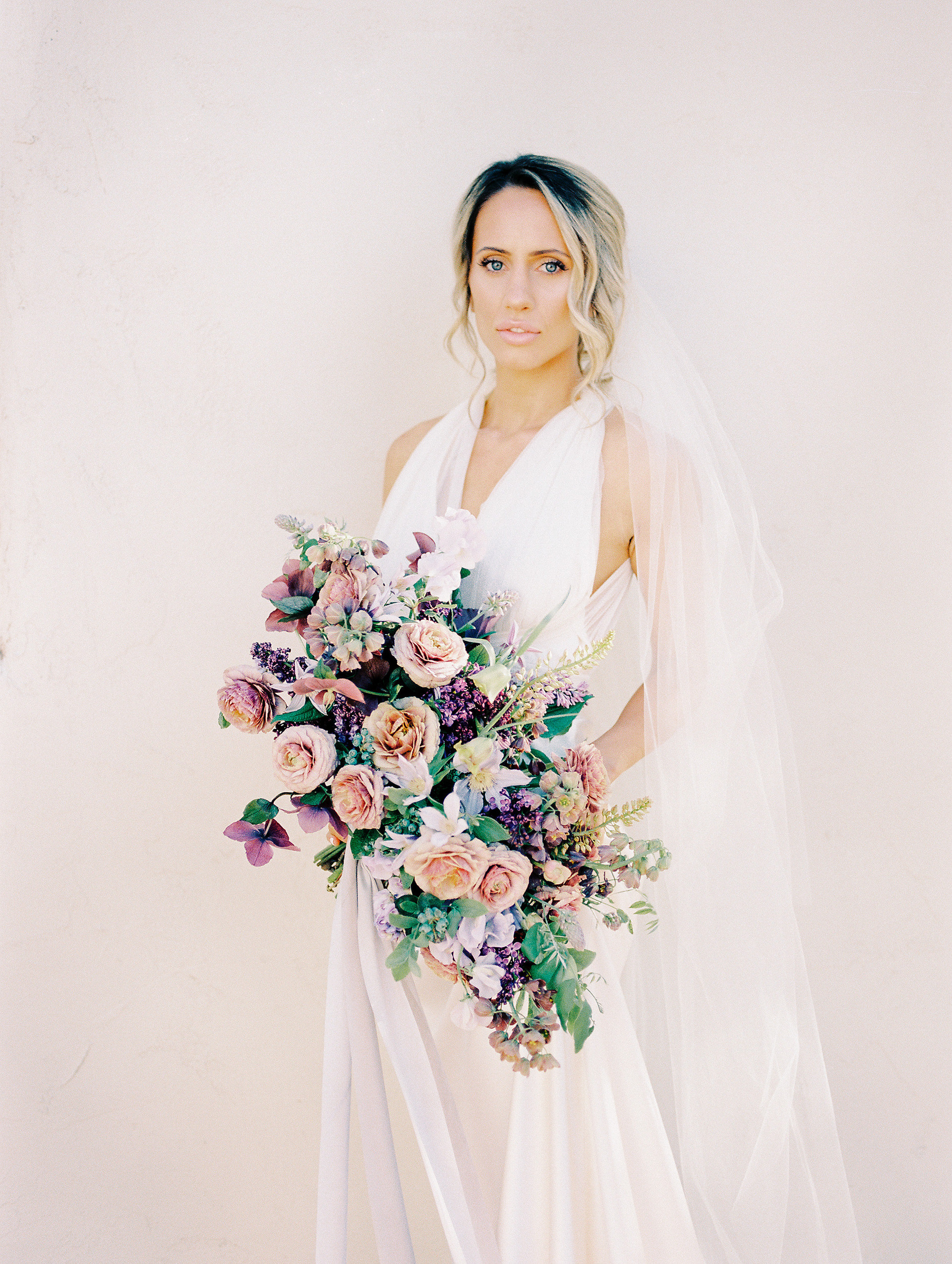 Mauve and plum bridal bouquet with lilac, sweet pea, ranunculus, fritillaria and hellebores. Photo: Shannon Elizabeth