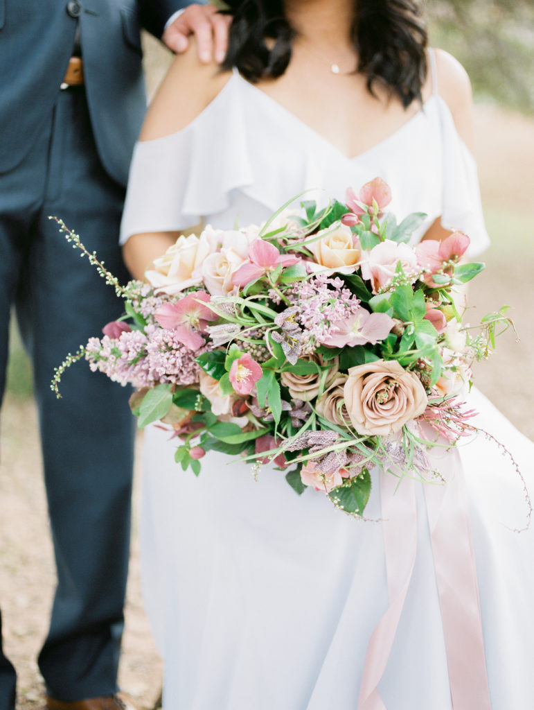 SPRING BRIDAL BOUQUET WITH GARDEN ROSES, LILAC, AND HELLEBORE, IN SHADES OF TAUPE, LAVENDER, AND DUSTY ROSE. PHOTO: LIANNA MARIE