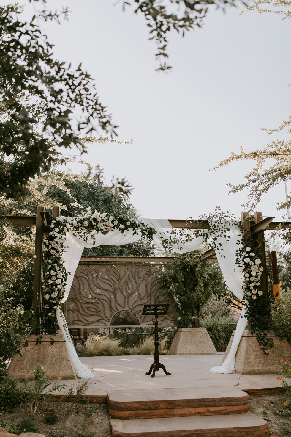 Wedding arch with fabric an floral. Photo: Courtney Pecorino