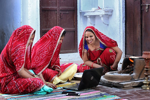 Three traditional Indian young married women working in traditional kitchen on laptop. Usi