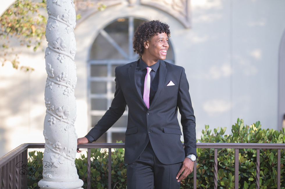 Guy in purple Prom tux inbetween trees at the Prada  in Balboa downtown San Diego Ca Ridgecrest Countryboiphotography.com