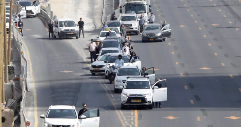 People standing still at the side of the road while siren sounds for yom hashoah