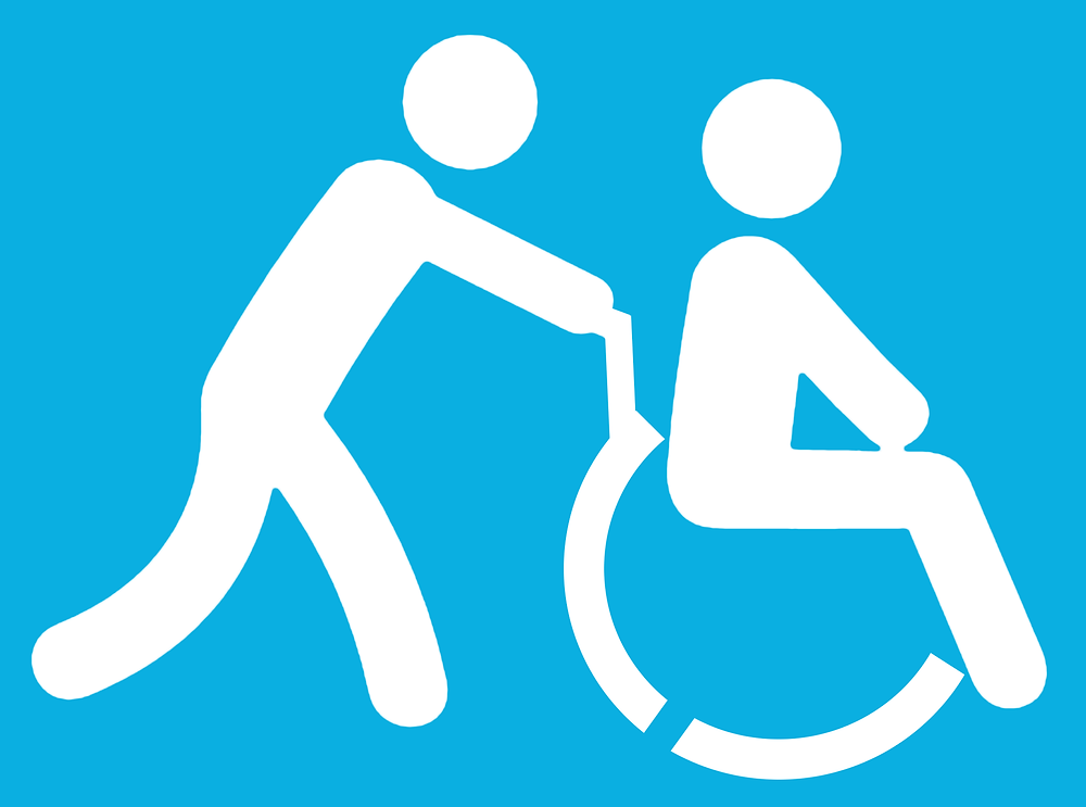 Symbol for disabled companion or caregiver, showing a stick figure pushing someone in a wheelchair.