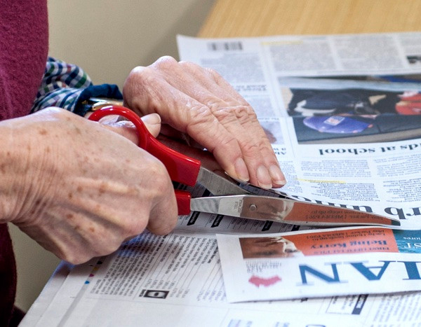 Stock photo of old hands cutting a newspaper.