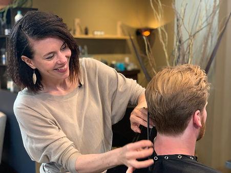 woman cutting man's hair, hairstylist, barber cutting man's hair, man getting a haircut, medium length haircut on man, modern mens styling