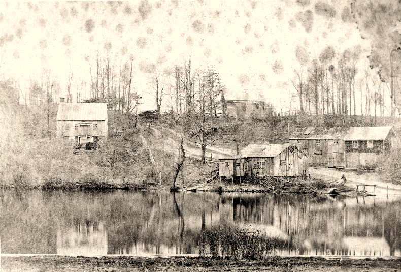 Property of Charles H & Sophia Jayne and son Charles E. Jayne. Harbor Rd overlooking the Stony Brook Millpond. LR: Jayne Home, blacksmith shop of Charles H. Jayne, wheelwright shop. Photo from the Rhodes Collection