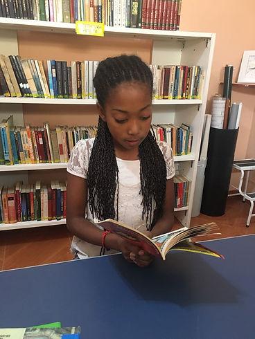 Criança lendo um livro do CLIS em uma biblioteca